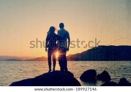 Young couple standing on the shore in the arms and looks at the setting sun by the sea. Filtered image: vintage, grunge and texture effects