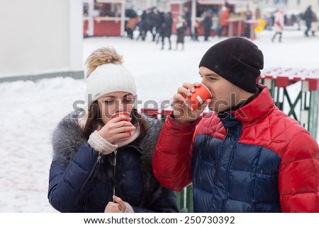 Young couple standing outdoors in an urban square in winter snow sipping hot drinks on a cold day from takeaway cups, people walking in the distance - stock photo