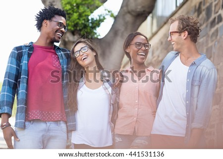 Young couple standing with arm around having fun - stock photo