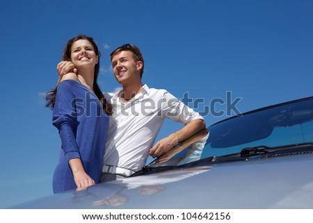 Young couple stands leaning a cabriolet windshield - stock photo