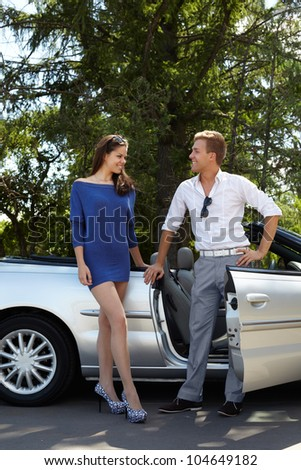 Young couple stands near cabriolet and talks - stock photo