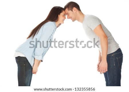 Young couple staring at each other and smiling / Happy couple looking at each other against white background - stock photo