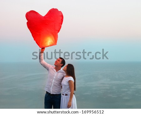 Young couple start a red Chinese sky lantern in the dusk near the sea - stock photo