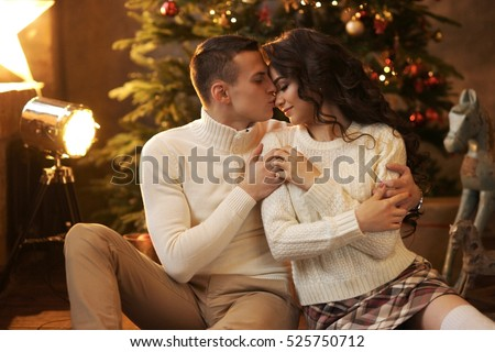 Young couple staying at home together on holiday evening and sitting on floor in front of christmas tree and hugging. Cute romantic lovers in white pullovers