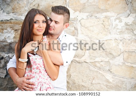 Young couple stood by stone wall - stock photo