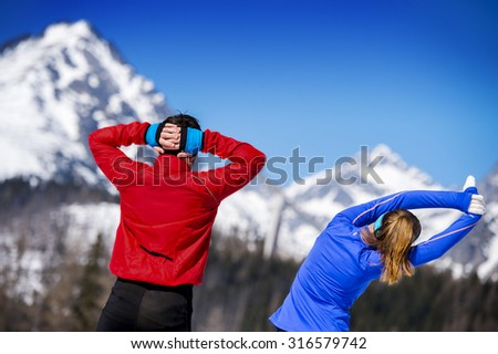 Young couple stretching before jogging outside in sunny winter mountains - stock photo