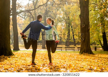 Young couple stretching legs before jogging in autumn nature - stock photo
