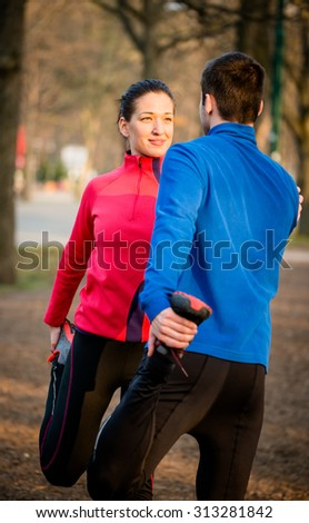 Young couple stretching muscles before jogging - outdoor in nature - stock photo