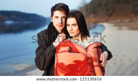 Young couple stying in the board of river. Cold spring outdoor portrait. - stock photo