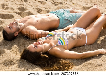 Young couple sunbathing on the sea sand summer day