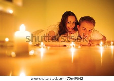 Young couple surrounded by candles on floor. Closeup, shallow DOF. - stock photo