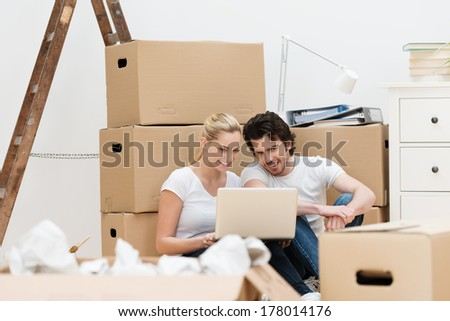 Young couple surrounded by packing boxes smiling as they use their laptop to make contact with friends while moving house - stock photo