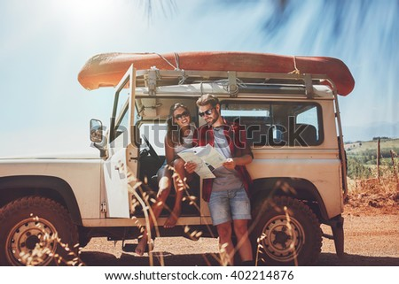 Young couple taking a break to look at a map while on a roadtrip. Young man and woman on country road looking for directions on map. - stock photo