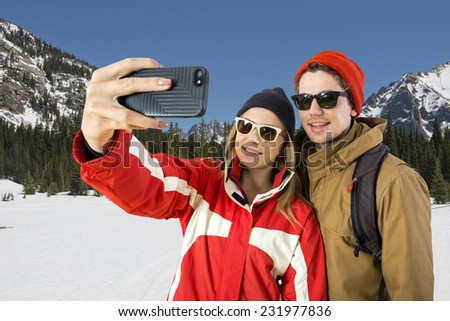 Young couple taking a selfie in front of a beautiful winter landscape during their wintersport - stock photo