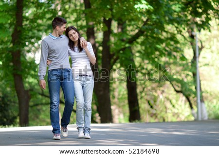 young couple taking a walk in the park - stock photo