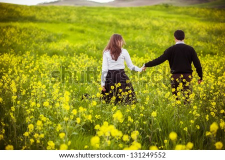 Young couple taking a walk on beautiful flower field. - stock photo