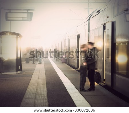 Young couple taking farewell in front of departing train at station on foggy day - stock photo