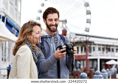 young couple taking pictures on holiday at tourist attraction - stock photo
