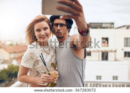 Young couple taking self portrait with smart phone during a party. Young man and woman taking selfie at rooftop party. Hanging out together on a weekend. - stock photo