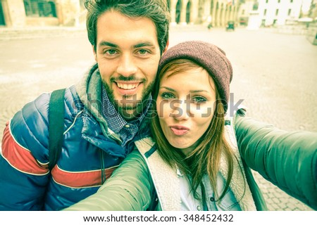 Young couple taking selfie by mobile phone in old city - Students teenager having fun with funny face expression for self photo with smartphone - Concept of joy and  memories vintage cold tones filter - stock photo