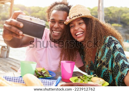 Young Couple Taking Selfie During Lunch Outdoors - stock photo