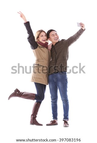 Young couple taking selfie in their winter clothes isolated on white - stock photo