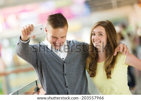 Young couple taking selfie with a cellphone in a shopping mall - stock photo