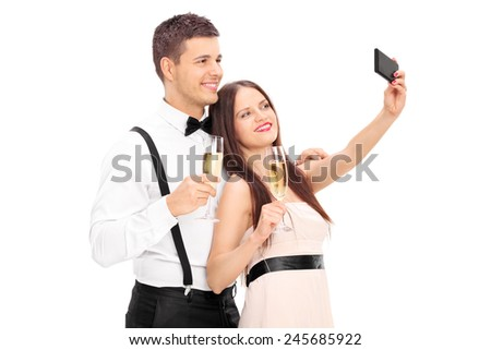 Young couple taking selfie with cell phone isolated on white background - stock photo