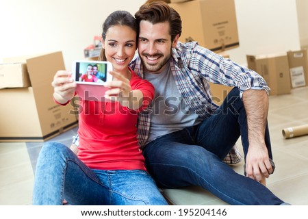 Young couple  taking selfies with her smartphone in their new home - stock photo