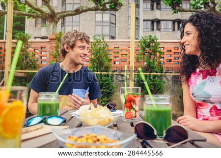 Young couple talking and laughing around the table with healthy drinks in a leisure summer day outdoors - stock photo