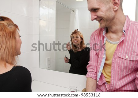 Young couple talking in hotel bathroom while woman is getting ready. - stock photo