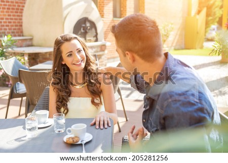 Young couple talking on the terrace of the restaurant, while eating - stock photo