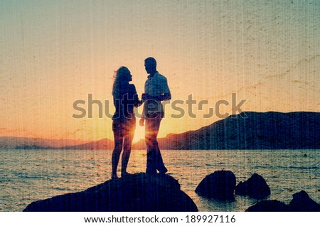 Young couple talking to a rock by the sea at the setting sun. Filtered image: vintage, grunge and texture effects - stock photo