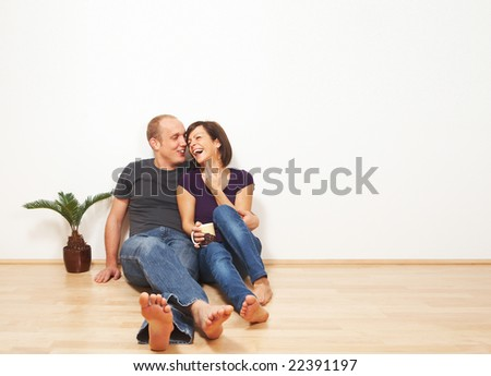 Young couple talking while sitting on the floor. Lots of copyspace. - stock photo
