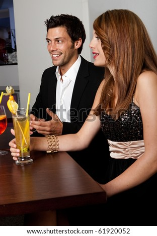 Young couple talking with friends at the restaurant or nightclub - stock photo