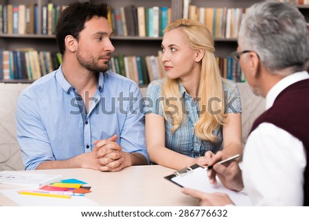 Young couple talking with psychologist. Psychologist taking notes. Man and woman looking at each other. There are many books in psychologist office - stock photo