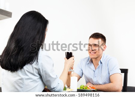 Young couple toast romantic date drink glass of wine, sitting table dinner, home or restaurant, celebrating valentine day - stock photo