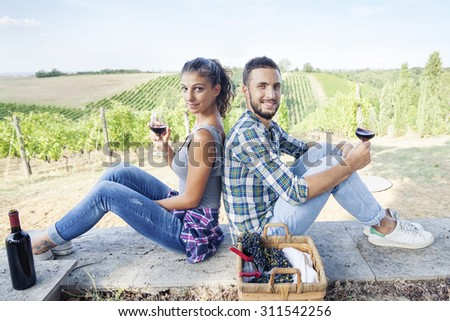 young couple toasting in a vineyard