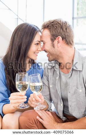 Young couple toasting wine glasses at home - stock photo