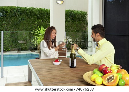 Young couple toasting with champagne in a modern backyard - stock photo