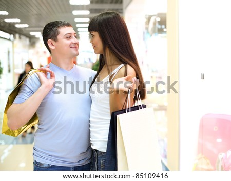 Young couple together doing shopping in the mall - stock photo