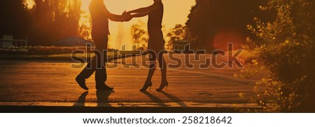 Young couple together in park during sunset on summer evening.  - stock photo