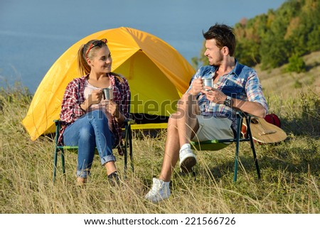 Young couple tourists, drinking tea near the tent camp - stock photo