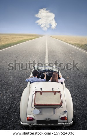 young couple traveling on a vintage car - stock photo