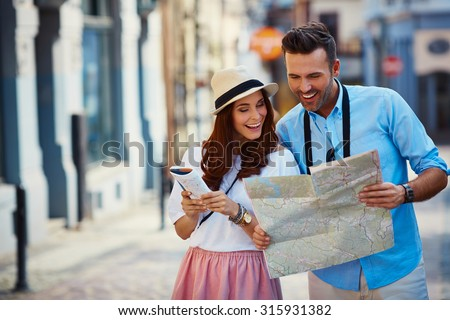 Young couple traveling, reading map in the city - stock photo