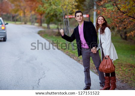 young couple traveling via hitchhike - stock photo