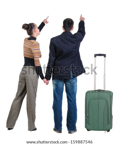 Young couple traveling with suitcas and  pointing at wall. Rear view. Isolated over white background. - stock photo