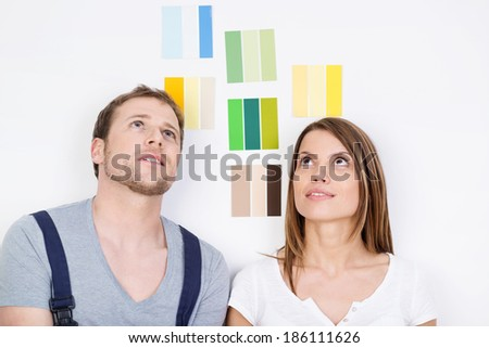 Young couple trying to decide on new interior decor for their home standing staring at the walls with an array of different coloured paint swatches behind them - stock photo