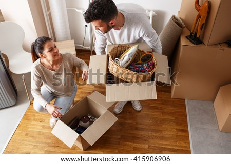 Young couple unpacking cardboard boxes at new home.Moving house. - stock photo