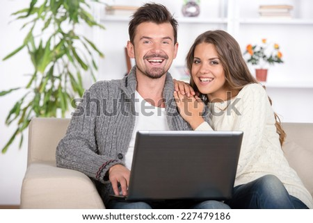 Young couple using a laptop computer at home - stock photo